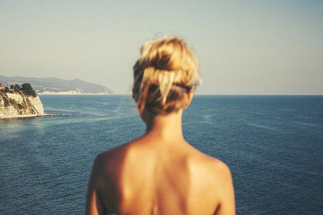 Detail na šiju ženy, ktorá stojí a pozerá na more.jpg
