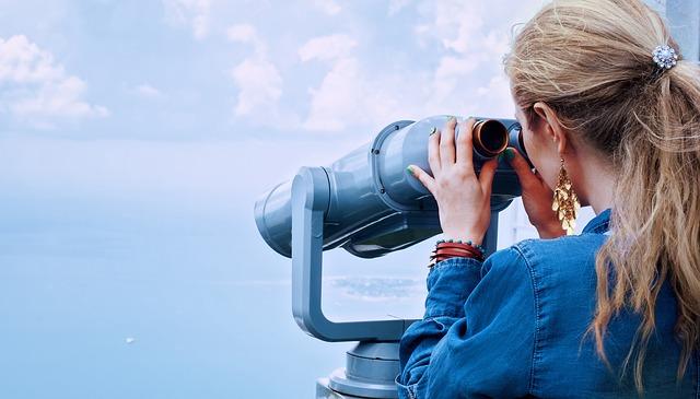 Žena v blond vlasmi a v rifľovej bunde pozerá do ďalekohľadu.jpg