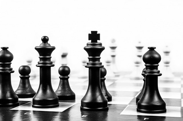 Čierne figúrky rozostavené na čierno-bielej šachovnici.jpg